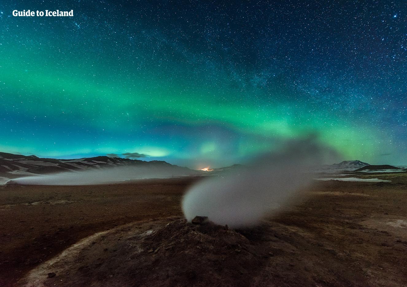 Het noorderlicht en een sterrenhemel boven een stoomopening in een geothermisch gebied bij het Mývatn-meer