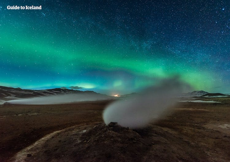Northern Lights and a starry sky over a steam vent in a geothermal area near Lake Mývatn