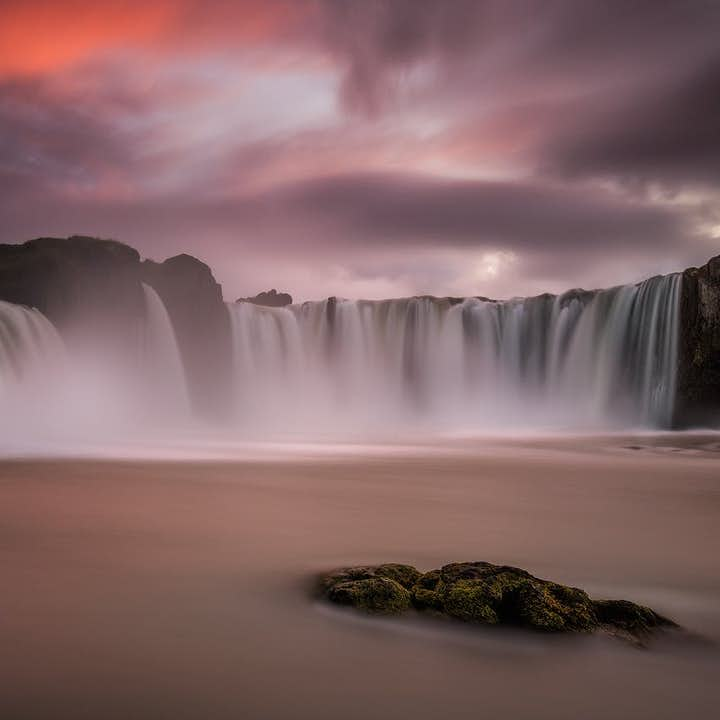 The spectacular, historic northern waterfall of Goðafoss under the midnight sun.