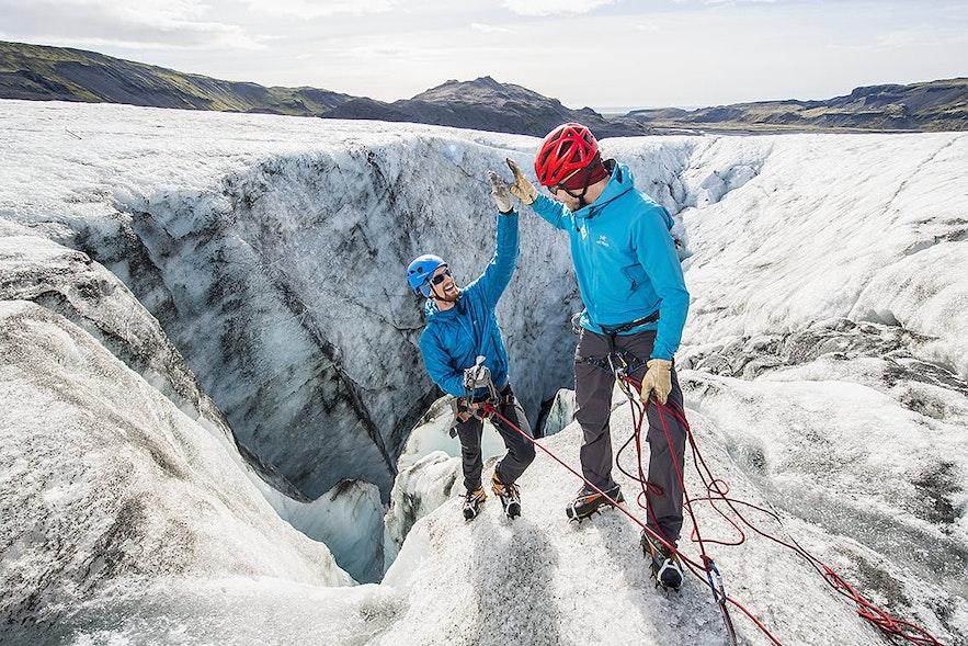 헬멧 아래 모자를 쓰고, 장갑과 방풍/방수 처리된 외투를 입은 후 튼튼한 등산화를 신은 두 관광객이 빙벽 등반 투어를 즐기는 모습입니다. 아이슬란드에서 필요한 옷차림을 가장 잘 보여주는 예라고 하겠습니다.