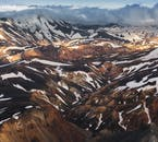 The Landmannalaugar mountains in the Highlands of Iceland, bathed in the sun and partly dressed in snow