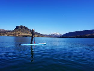See blue mountains in the distance as you stand on a paddleboard on Hvalfjörður fjord.