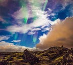 The Northern Lights over a moss-covered lava field.