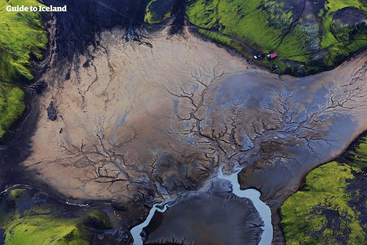 Green, mossy hills surround a black desert in the Icelandic Highlands.