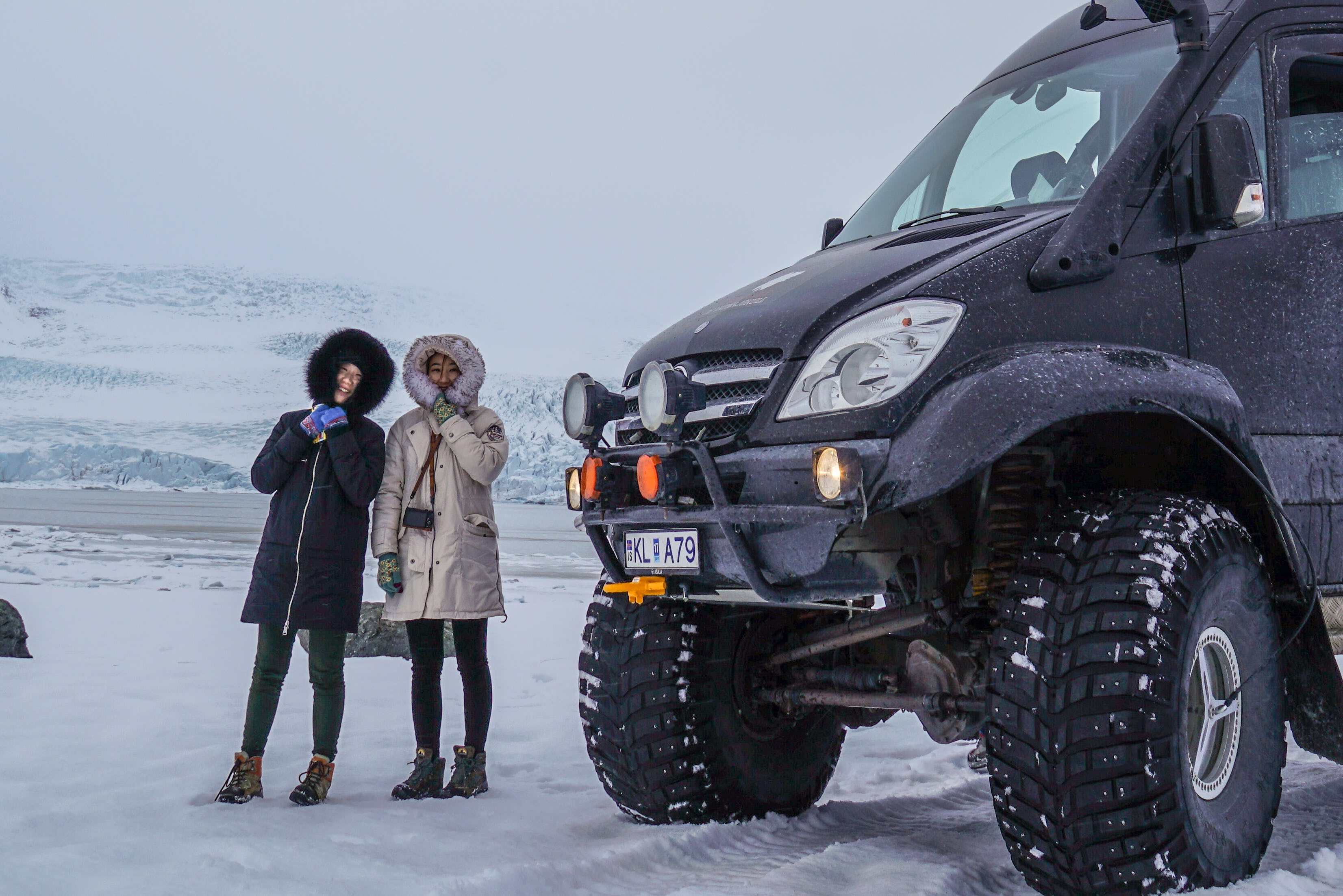 Two adventurers next to the massive superjeep used to get the ice caves high in the mountains.