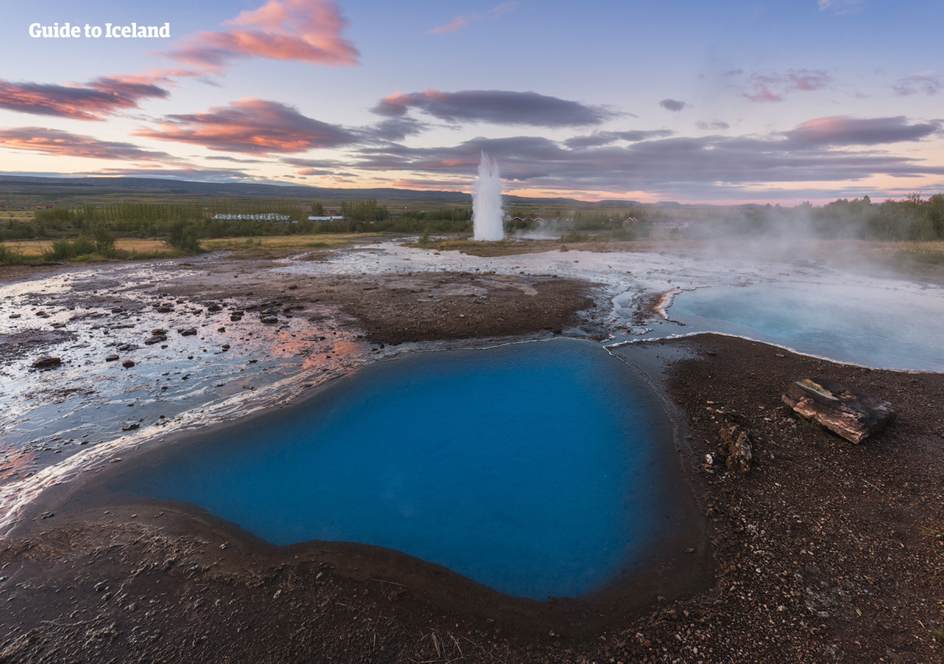 The geyser Strokkur in front of azure coloured fumaroles in the geothermal valley Haukadalur in South Iceland.