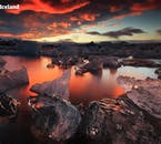 The glacier lagoon Jökulsárlón drenched in the scarlet hues of the Icelandic summer night.