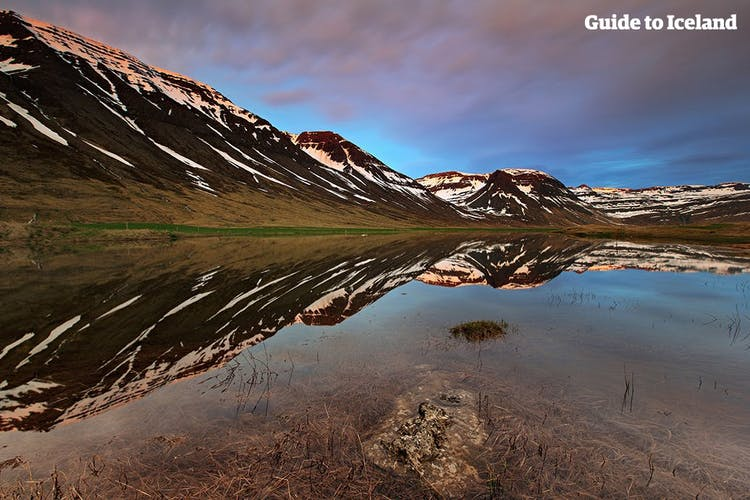 Mountains of the Westfjords reflect in the sea under the midnight sun.