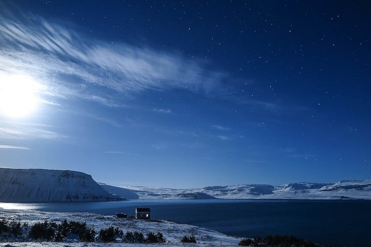 A stunning sky with the midnight sun and stars over the Westfjords in summer.