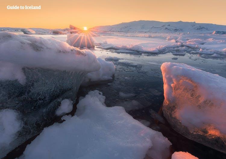 A scenic winter sunrise at Jökulsárlón glacier lagoon in Iceland's Vatnajökull National Park.