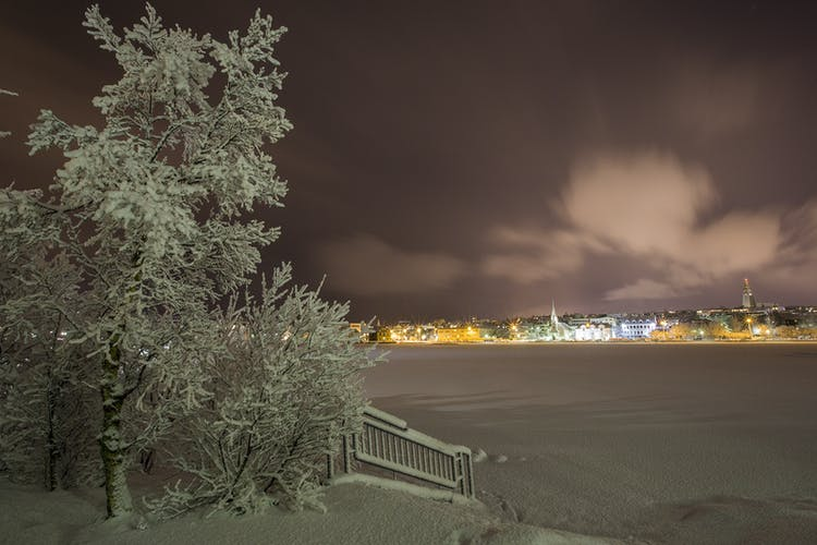 The Reykjavík City pond, Tjörnin, covered with ice and snow, with the old capital lighting up the dark winter sky.