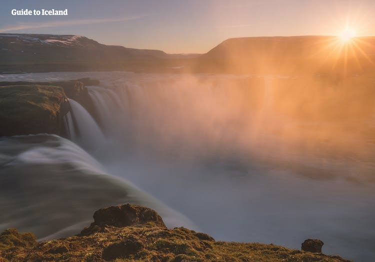 The blinding lifht of the midnight sun in Iceland casting its colours upon the waterfall Goðafoss in the North.