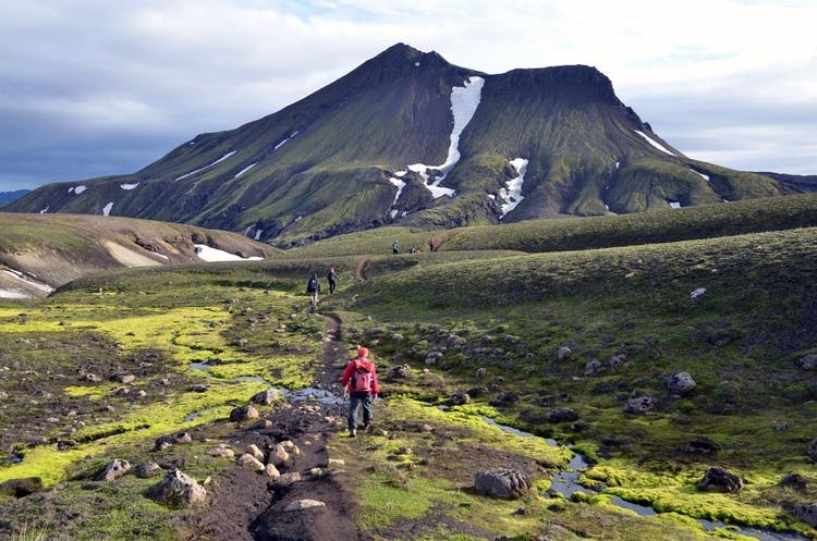 Hikers in front of the distinctive mountain Brattháls in the Highlands of Iceland.