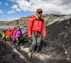 You can see white ice, black sand and green hills on a glacier hiking tour on Sólheimajökull glacier