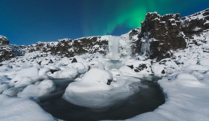 Öxarárfoss waterfall in the snow-covered Þingvellir National Park during winter time.