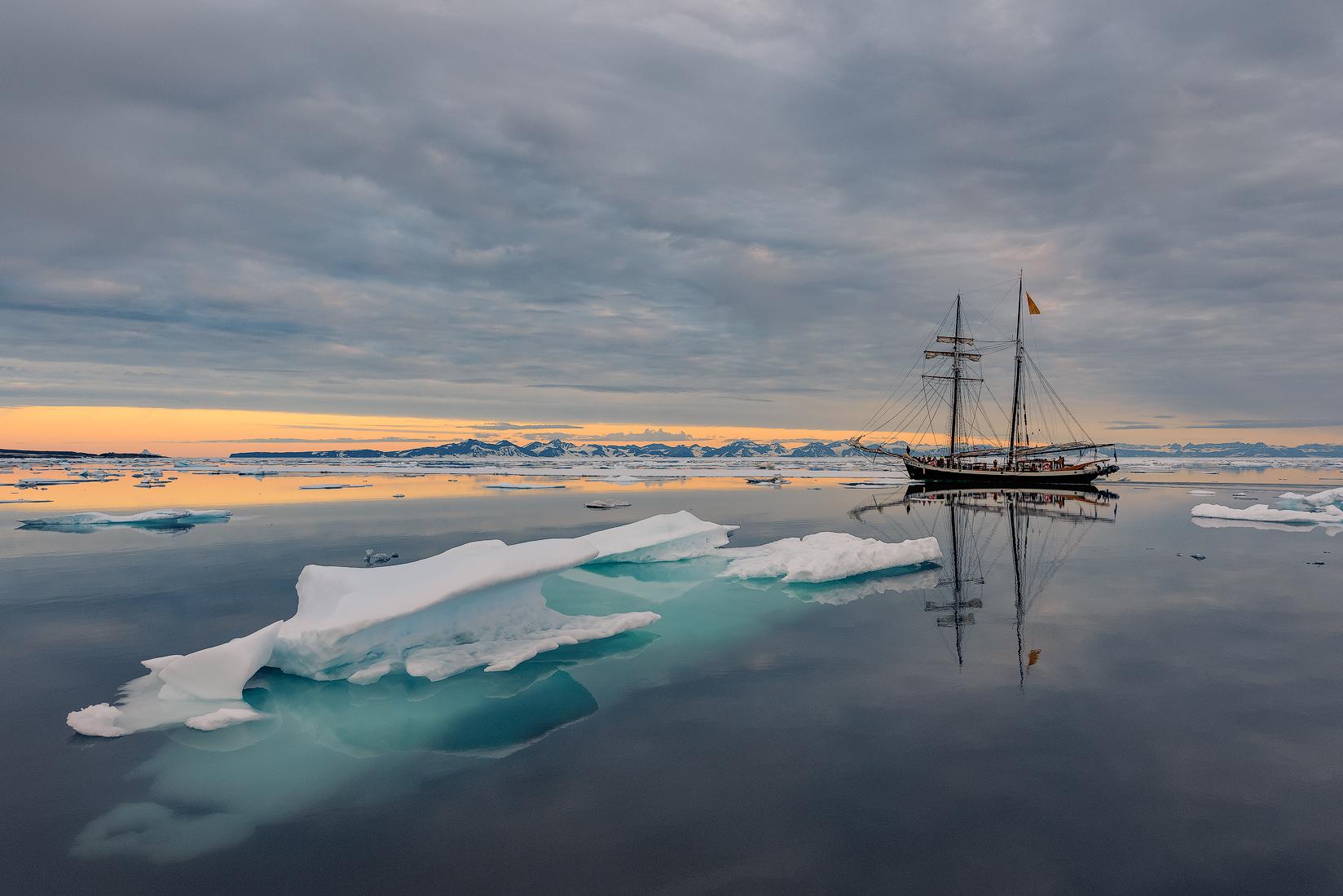 唐娜木船静静地驶过格陵兰岛海岸的冰山