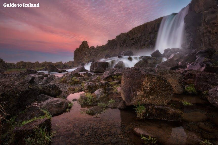 The midnight sun gleams on Þingvellir National Park's waterfall Öxaráfoss.