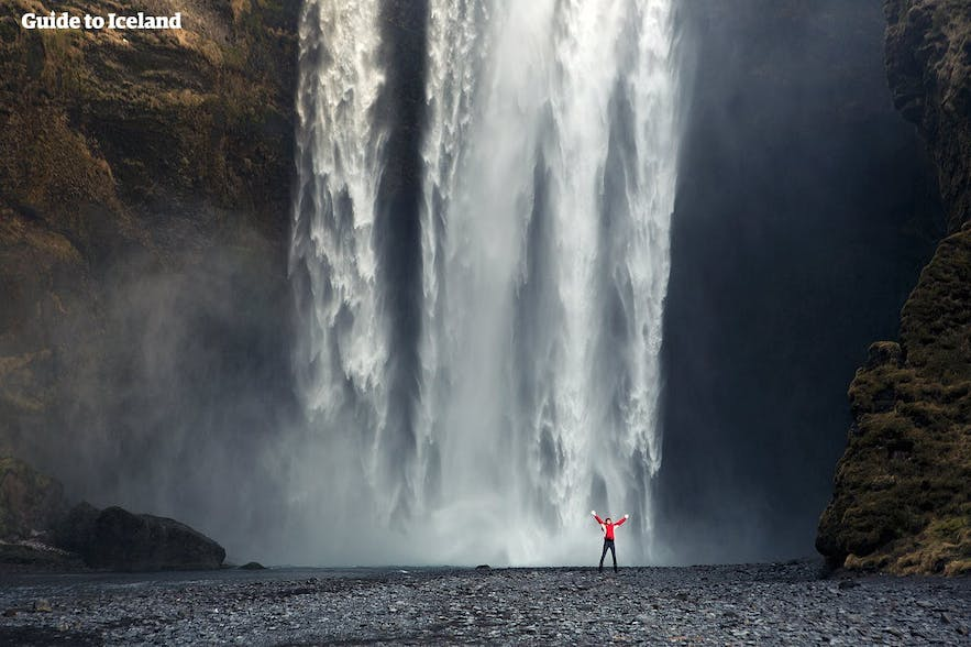 Traveller throwing their hands in the air in front of the thundering cascade of Skógafoss Waterfall.