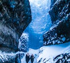 Witness the electric blue ice walls, blackened by ash from past volcanic eruptions on an ice cave tour.
