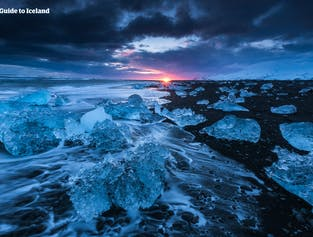 Auf einer Mietwagen-Winterreise kannst du den Diamantstrand am Abend besuchen und zuschauen, wie die Sonne zwischen den glitzernden Eisbergen untergeht.