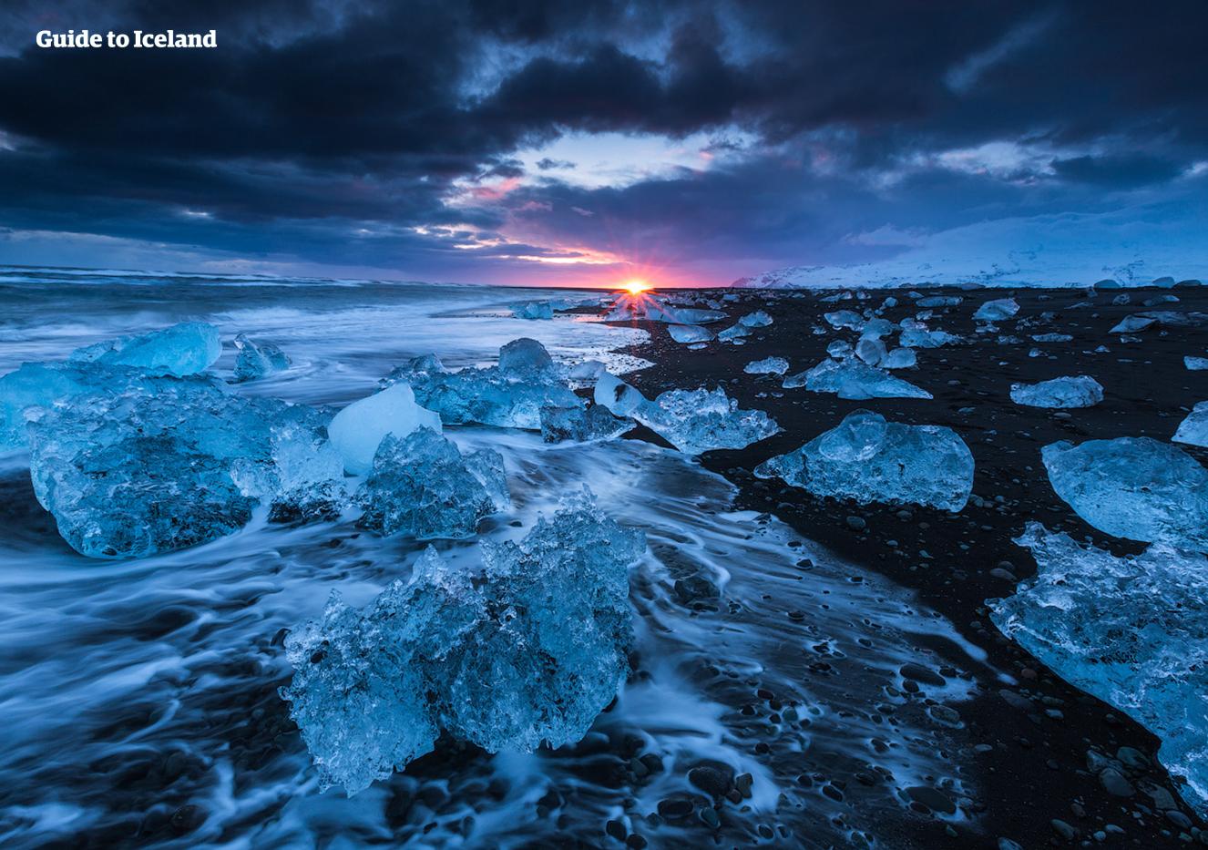 Tijdens een autorondreis in de winter kun je 's avonds Diamond Beach bezoeken om te zien hoe de zon ondergaat tussen glinsterende ijsbergen.