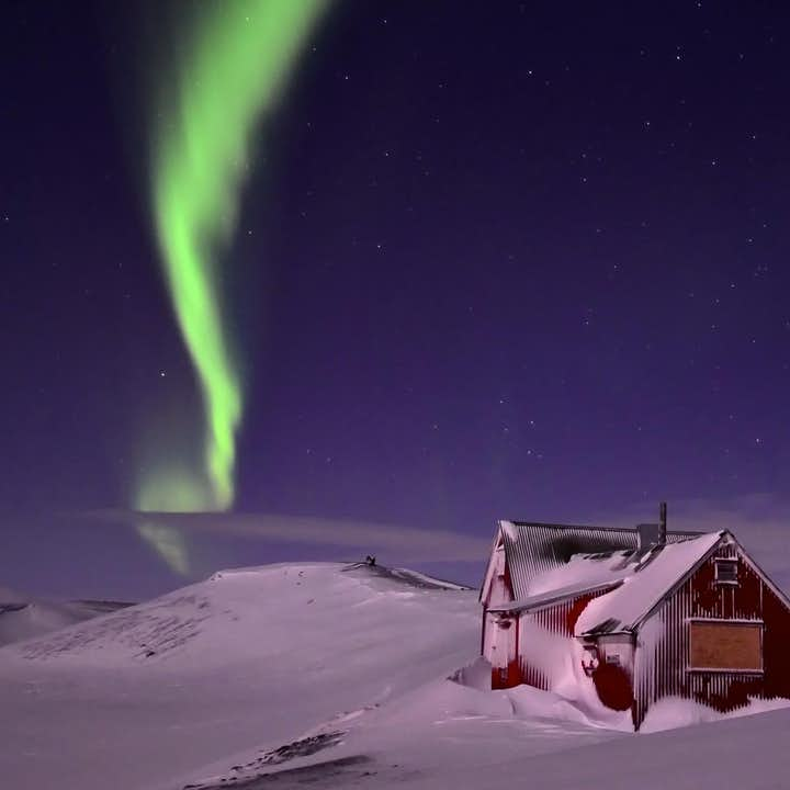 The Northern Lights dancing over a cabin in the barren Icelandic highlands.