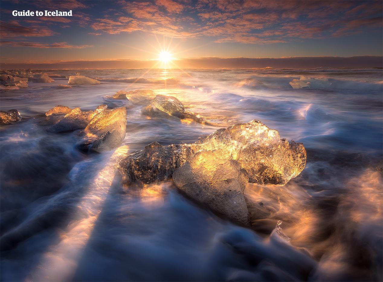 Eisberge glitzern unter der tiefstehenden Sonne am Diamantstrand in der Nähe der Gletscherlagune Jökulsarlon.