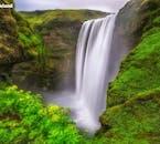 Der Wasserfall Skogafoss an Islands Südküste ist von üppiger Vegetation umgeben.