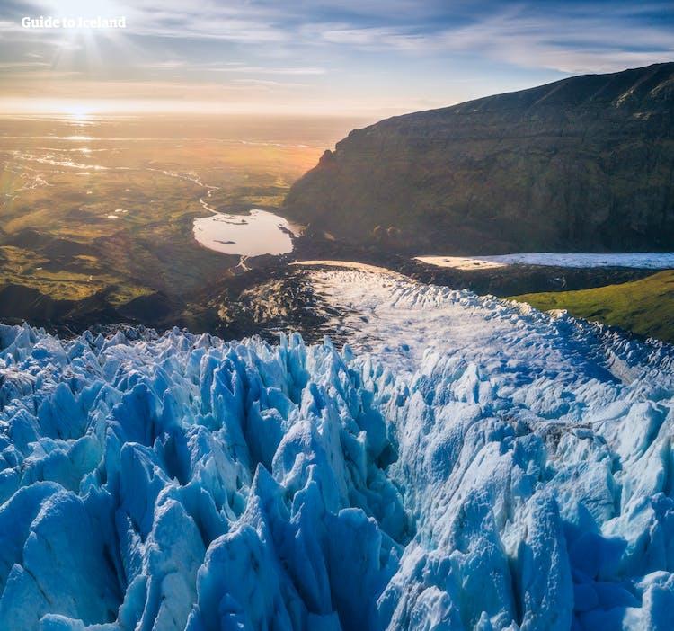 氷河の青と、太陽光の金色の光のコントラストが美しい南海岸の風景
