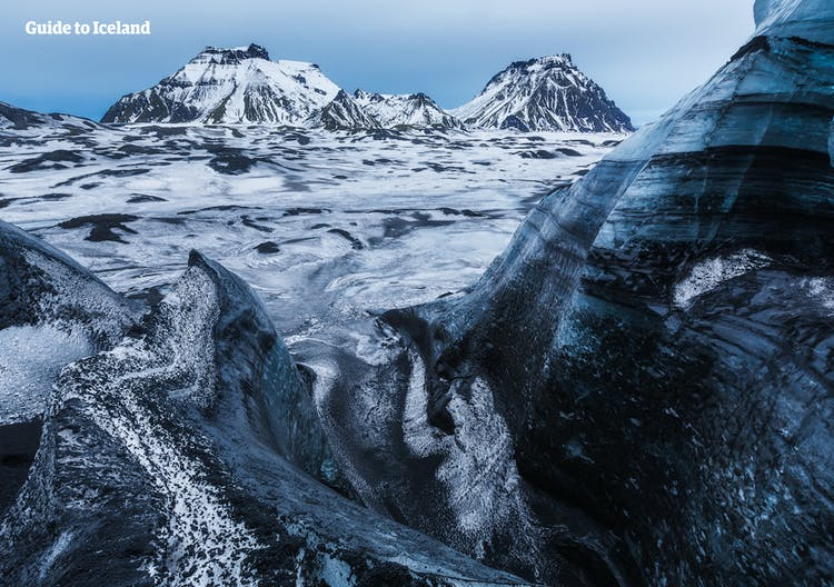 Mýrdalsgjökull's glacier peaks are covered in black ash from past volcanic eruptions.