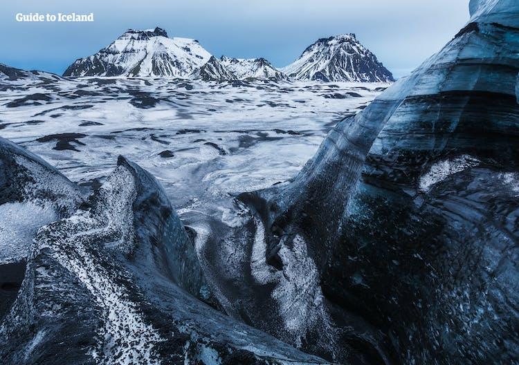 Mýrdalsgjökull's glacier peaks are covered in black ash from past volcanic eruptions.