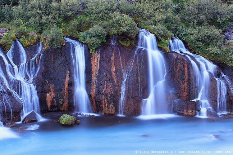 Hraunfossar is a series of gentle waterfalls pouring from a lava field.