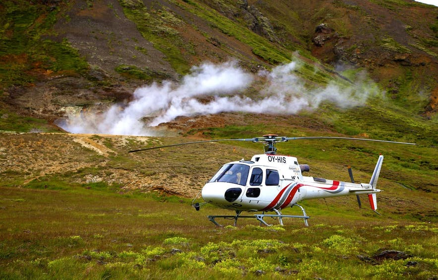 A helicopter making a landing at one of Iceland's geothermal valleys.