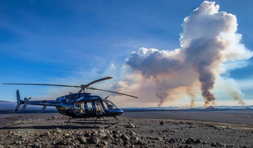 A helicopter overlooking the flaming crevasses of Holahraun Lava Fields.