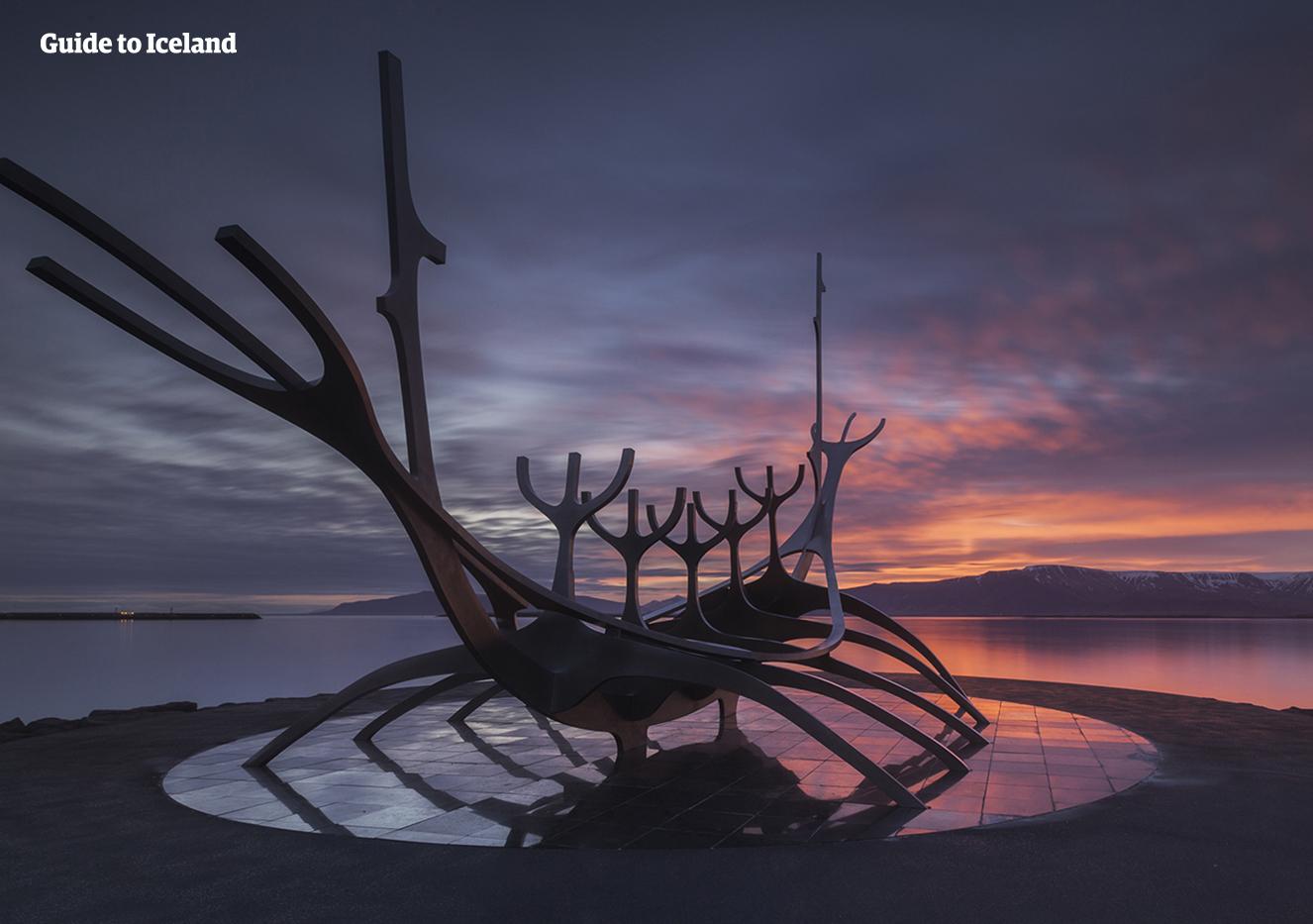 Beobachte von einem Platz neben der Skulptur Sun Voyager in Reykjavik, wie sich die Sonne hinter dem Berg Esja versteckt.