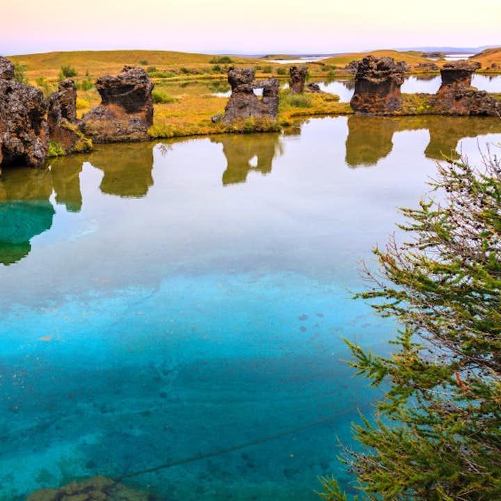 Lava pillars reflecting in the aquamarine waters at Lake Mývatn.