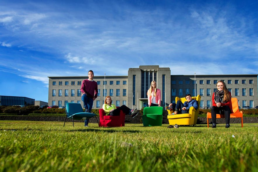 Students posing outside of the main building of the University of Iceland.