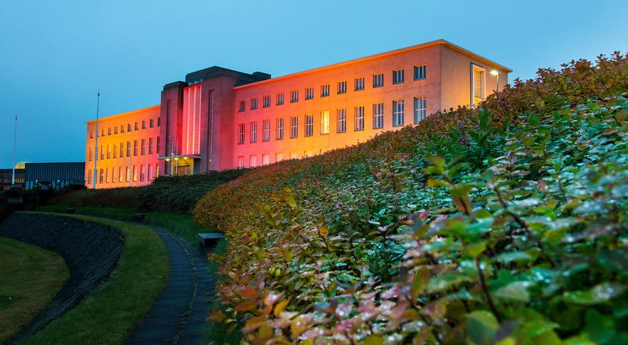 The main university building illuminated at night.