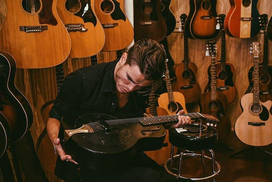 Kaleo's lead vocalist, JJ Julius Son, appreciating a large guitar collection.