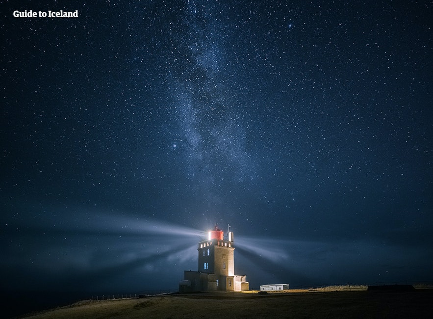 The lighthouse at Dyrhólaey shining under a starlit sky.