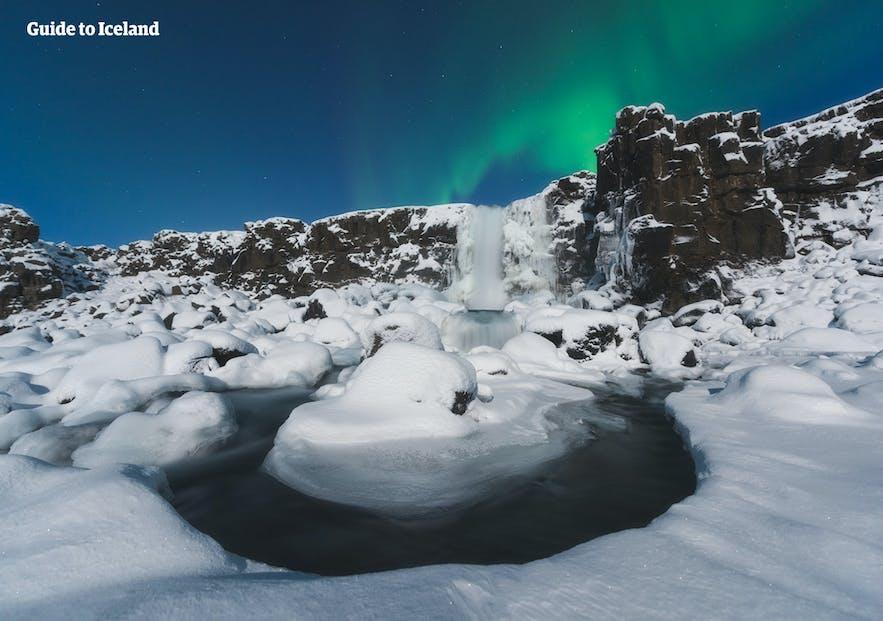オーロラに照らされた冬のオクサルアゥルフォスの滝(Öxarárfoss)me,