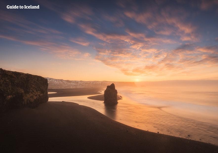 Den svarte sandstranden Reynisfjara. Du kan se steinsøylen Reynisdrangar midt på bildet.