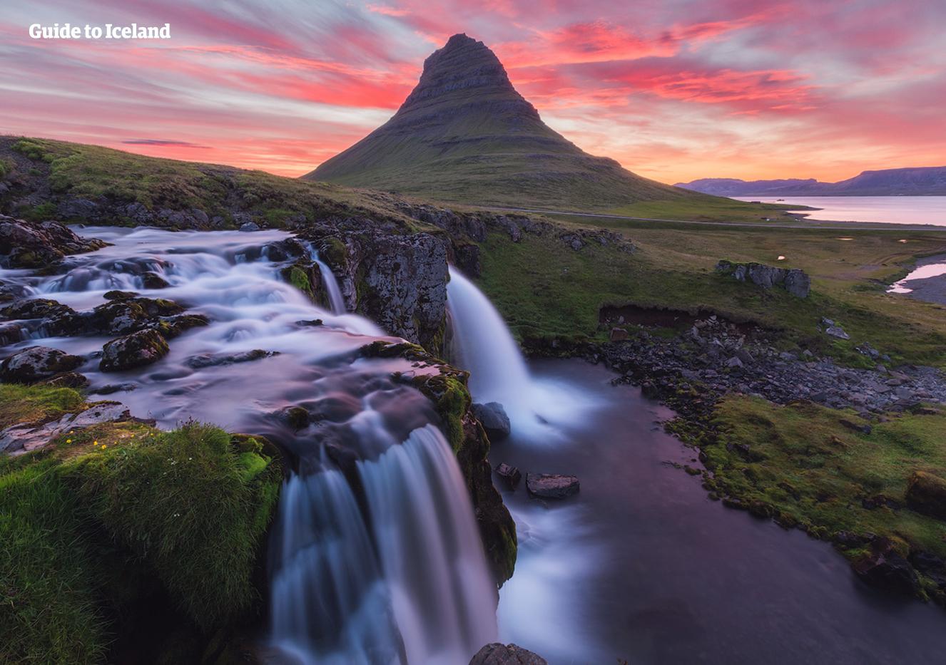 Le mont Kirkjufell en forme de pointe de flèche sur la péninsule de Snæfellsnes, baigné par les rayons du soleil de minuit.