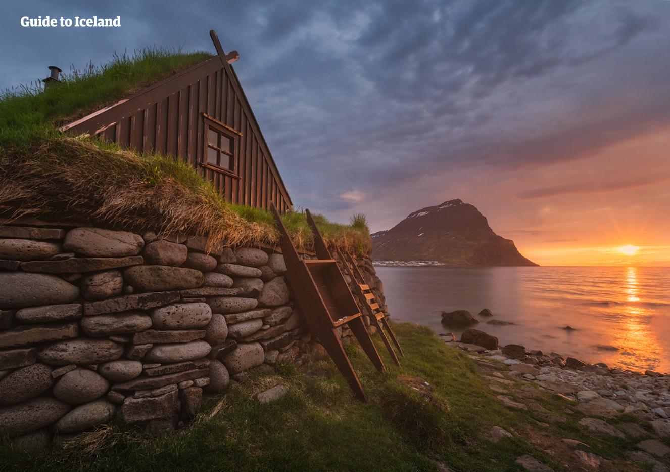 Maisons aux toits recouverts d'herber sous le soleil de minuit, dans la région des fjords de l'Ouest.