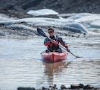 Paddle on the calm water of Sólheimajökull glacier lagoon on a kayaking tour.