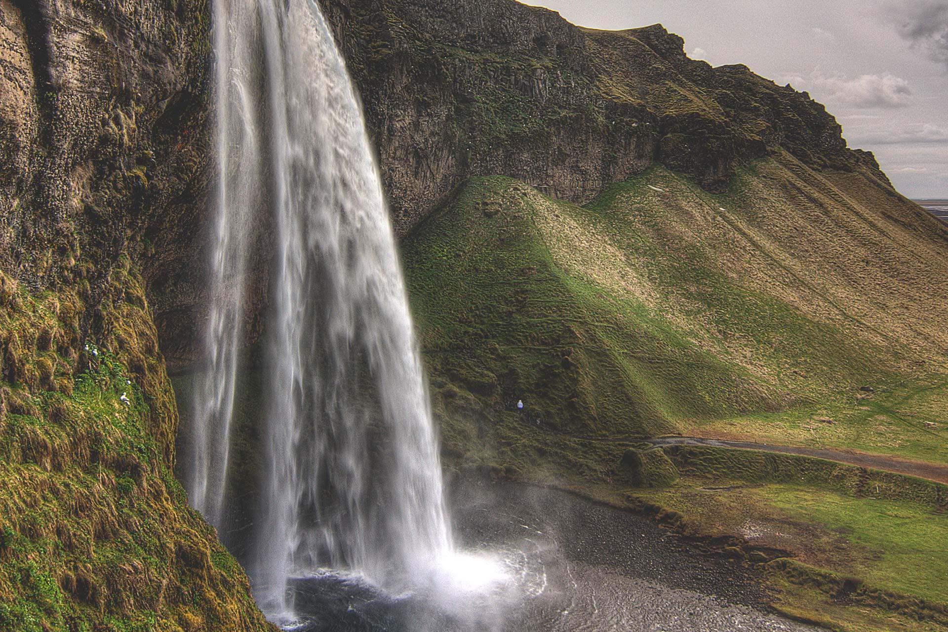 Zobacz kaskadę wodospadu Seljalandsfoss spływającą po klifach na południowym wybrzeżu Islandii.