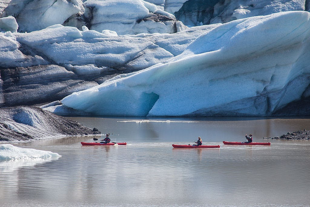 Wiosłuj między górami lodowymi podczas spływu kajakowego laguną lodowcową Sólheimajökull.