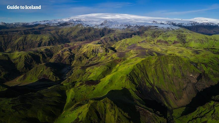 コケで覆われたアイスランドの山の向こうには氷河が見える