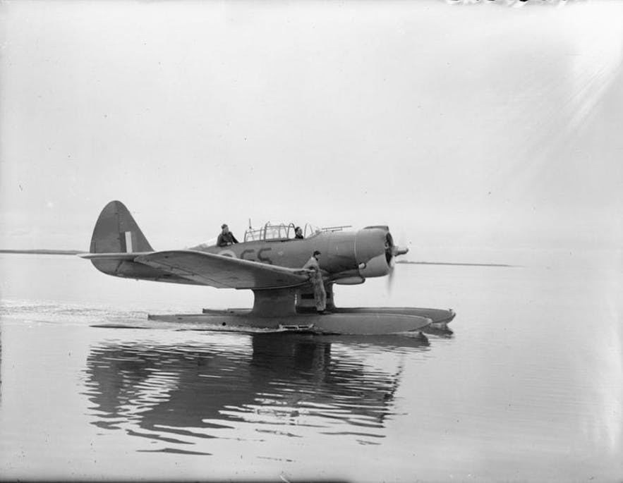 A Northrop N3P-B aircraft, floating in the water at Akureyri, October 1941. An engineer stands on the plane, ready to check its engines.