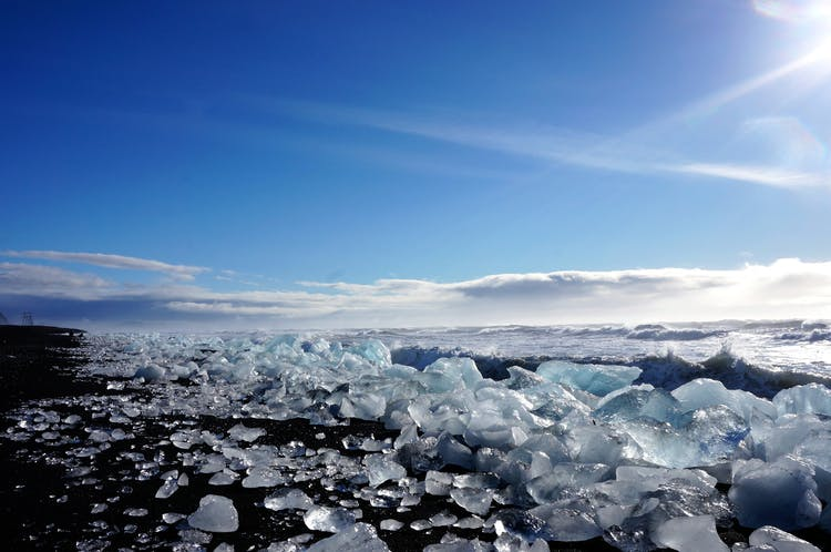 햇살에 눈부시게 빛나는 빙하가 가득한 다이아몬드 해변의 흑사장